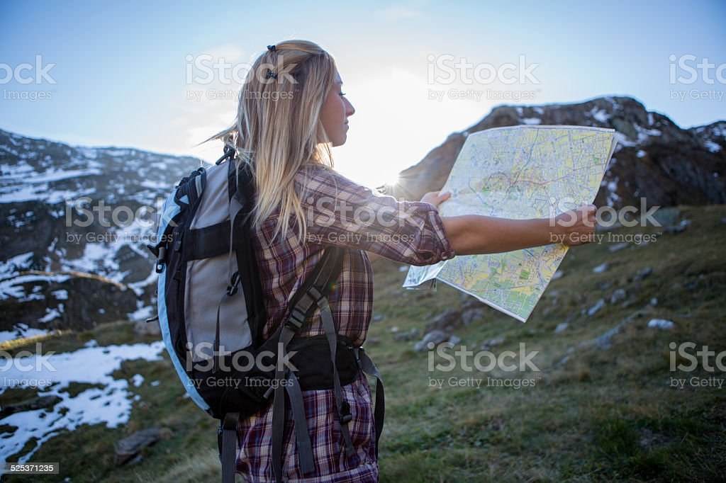 Young woman hiking in high mountains in Autumn reading a map to find...