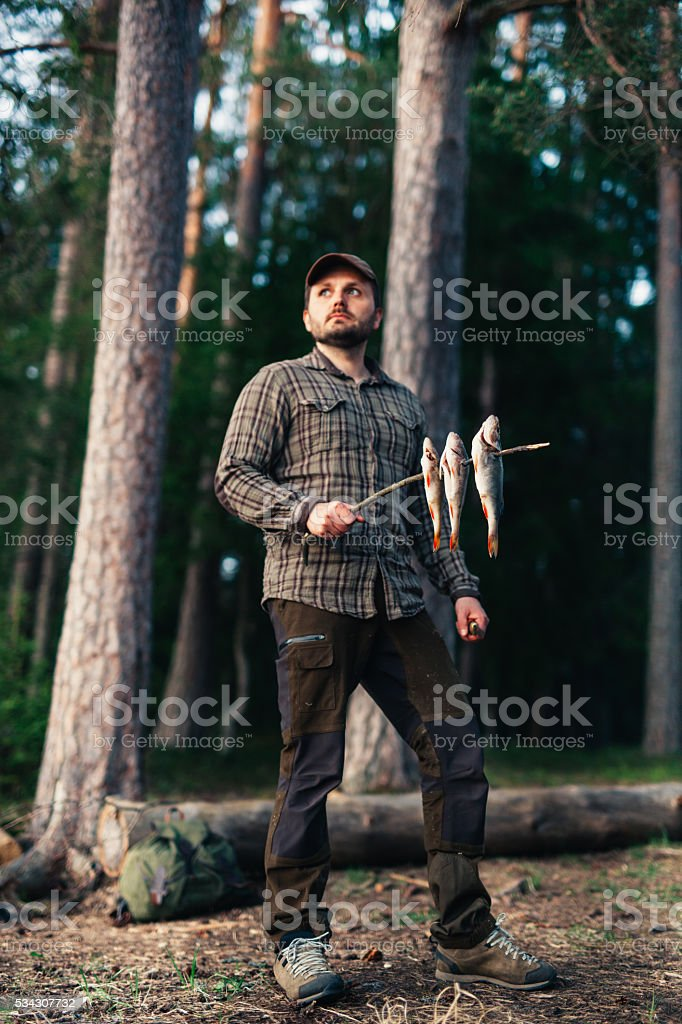 Hiker Getting Ready To Cook Raw Fish stock photo
