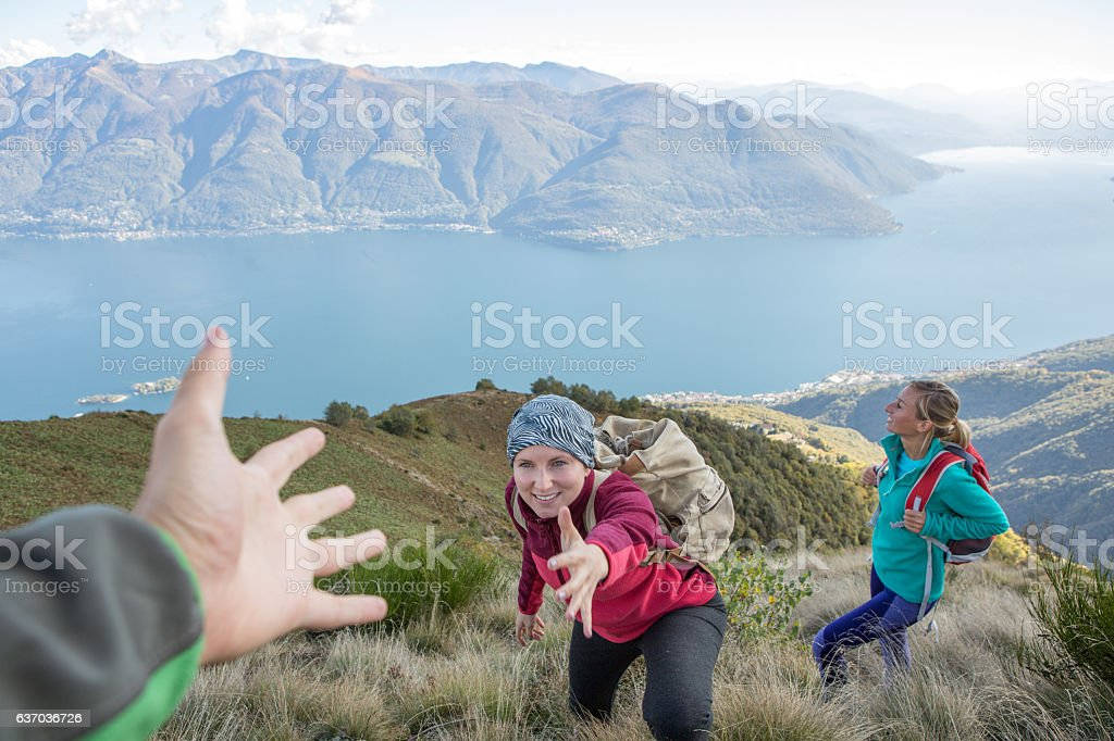 Hiker giving helping hand to teammate stock photo