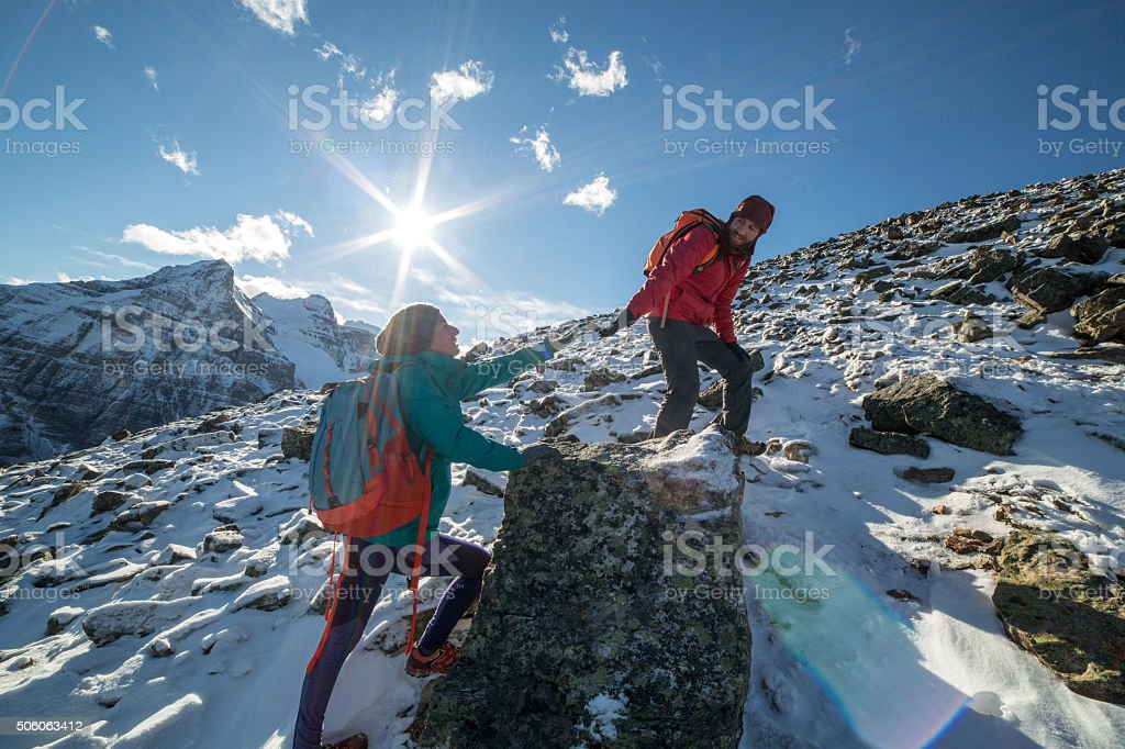 Hiker helping partner stock photo