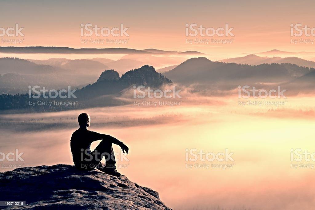 Hiker in black on rocky peak. Wonderful daybreak in mountains stock photo