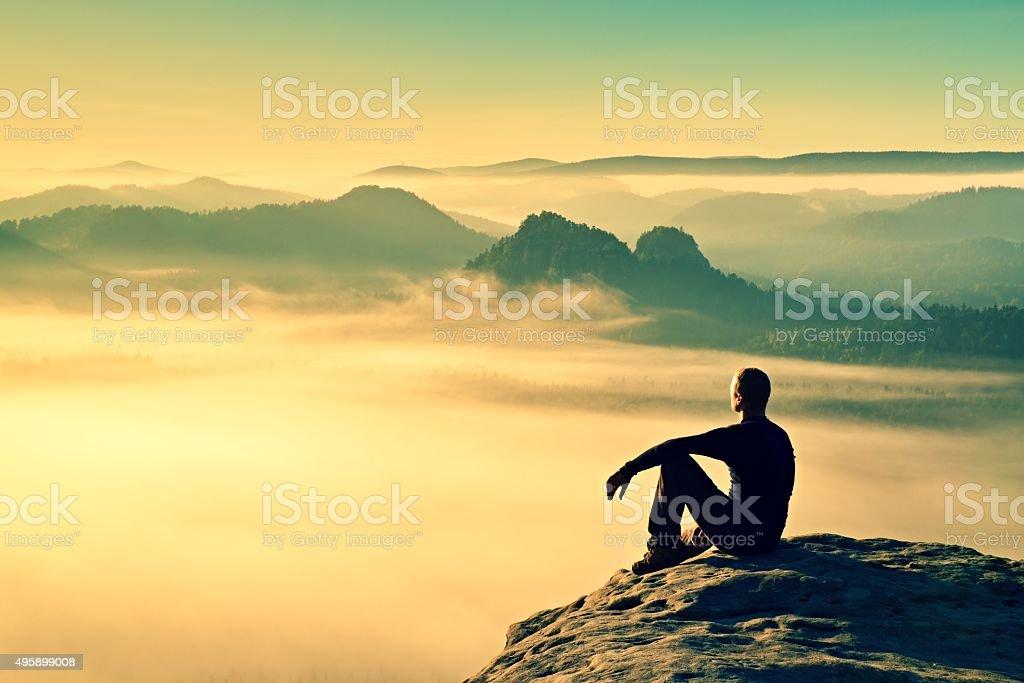 Hiker in black. Wonderful daybreak in misty mountains stock photo