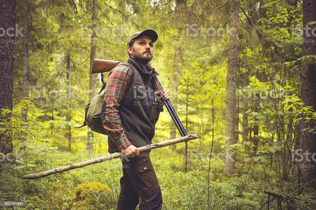 Hiker in Forest with Shotgun and Walking Cane stock photo