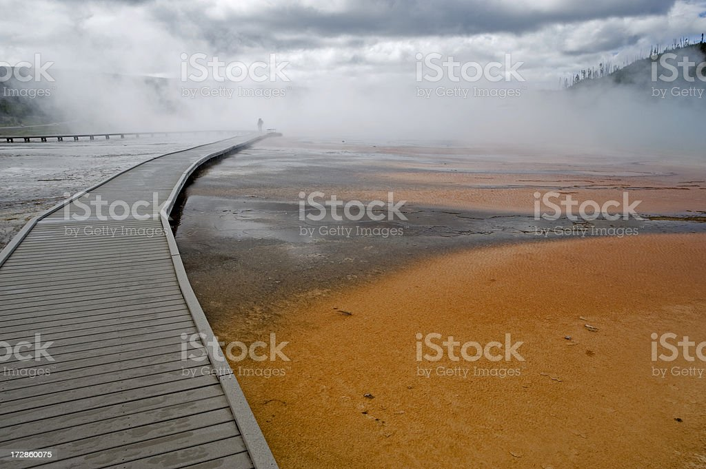 Hiker in mist on boardwalk of the Grand Prismatic Spring stock photo