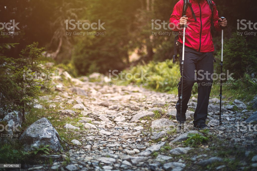 Hiker in red jacket walks alone on a mountain trail stock photo