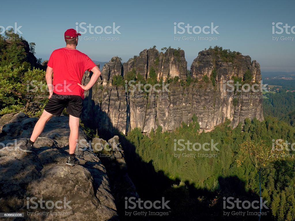 Hiker in red shirt and pants. Man on sandstone cliff stock photo