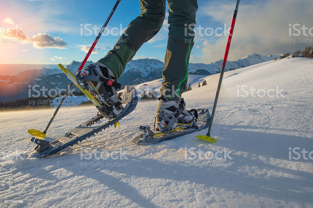 Hiker in spring mountains snowshoeing stock photo