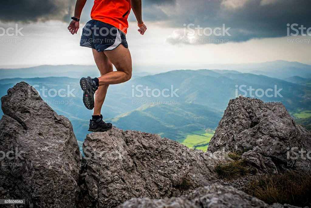 Hiker Jumping from One Rock to Another stock photo