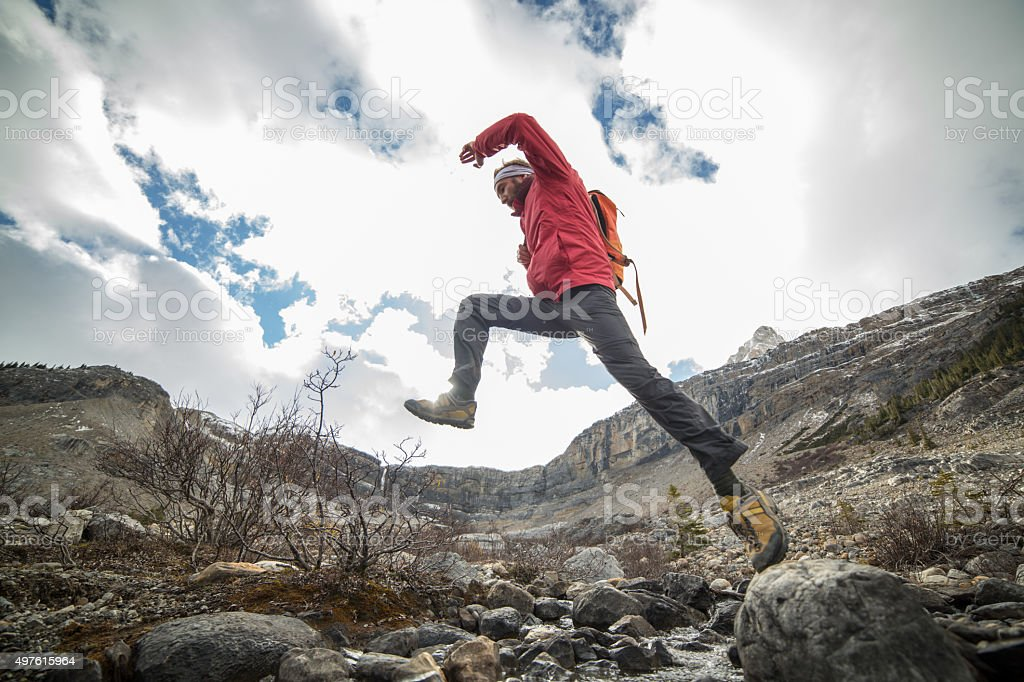 Hiker jumping over mountain river stock photo