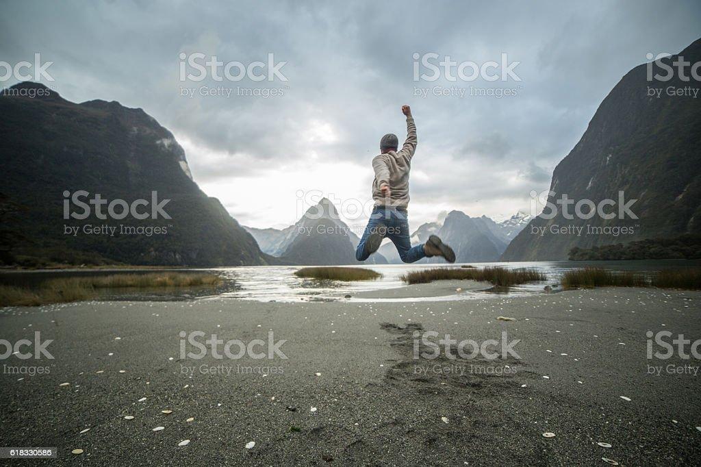 Hiker jumps mid air, New Zealand stock photo