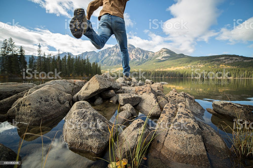 Hiker jumps rock to rock in mountain lake stock photo
