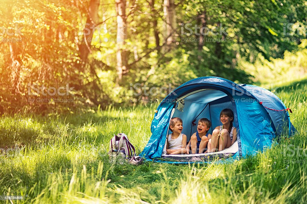 Hiker kids sitting in tent in the forest stock photo