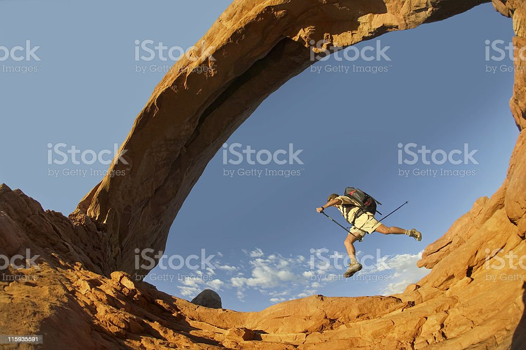 Hiker Leaping from Rock  under Arch stock photo
