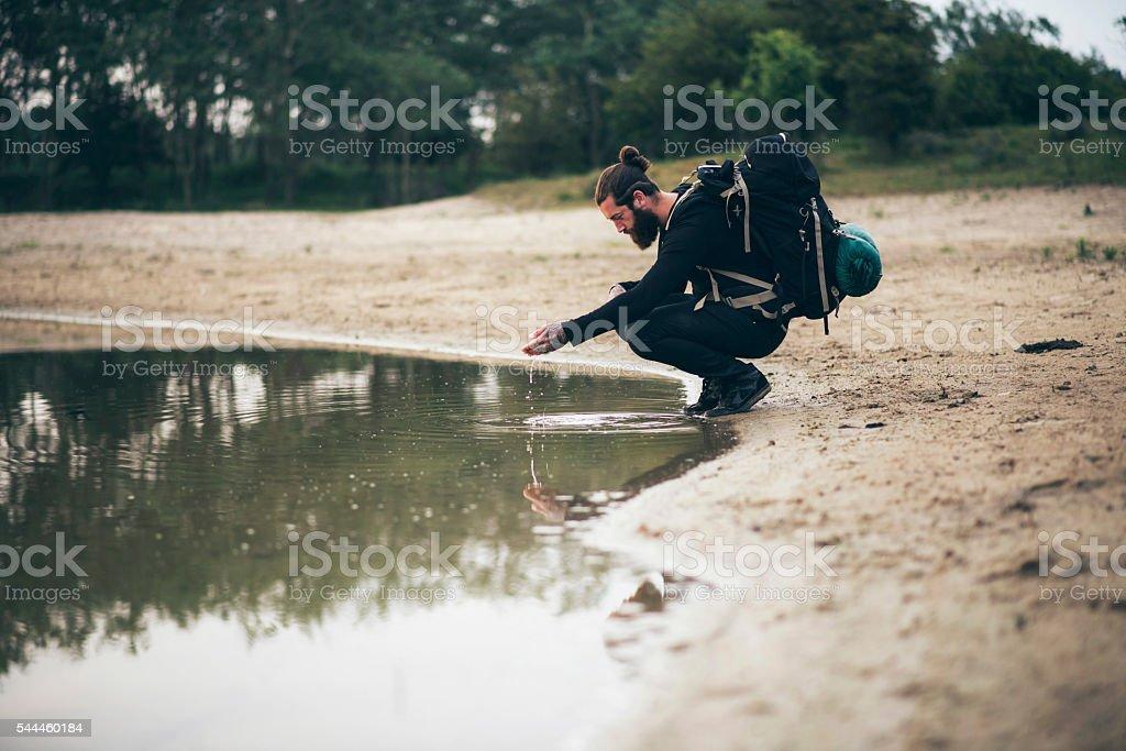 Hiker lets water run through hands stock photo