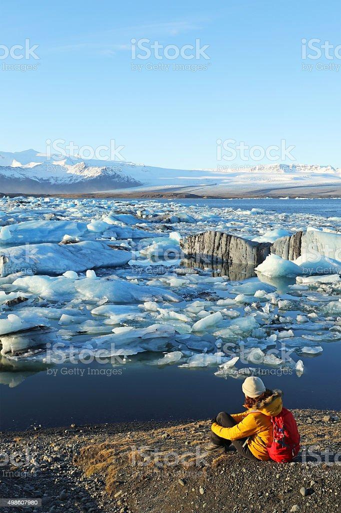 Hiker Looking at Drifting Icebergs at Jokulsarlon Glacial Lagoon Iceland stock photo