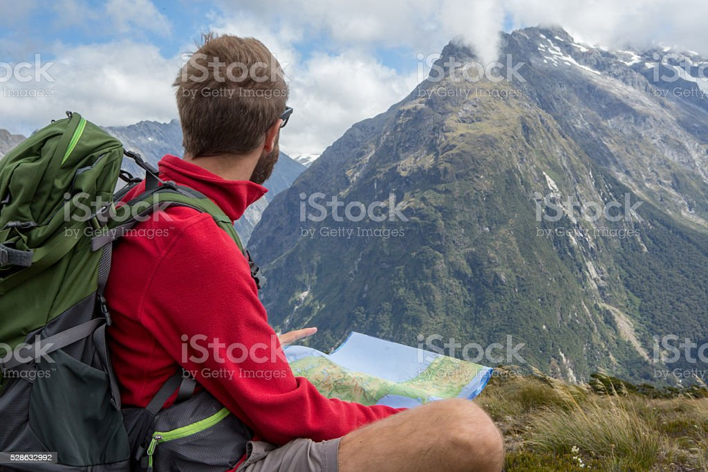 Young male hiker sits on a rock and looks at a trail map for...