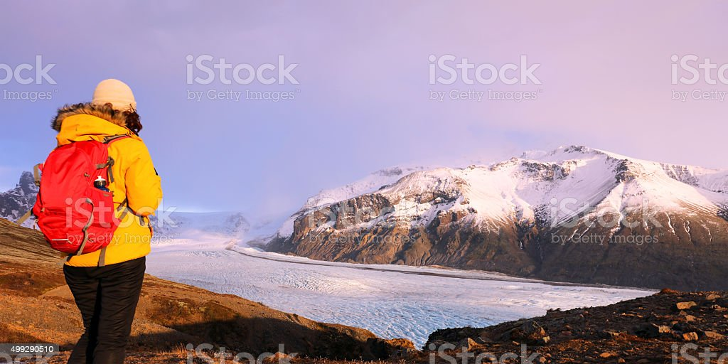 Hiker Looking at Skaftafell Glacier at Sunset in Winter Iceland stock photo
