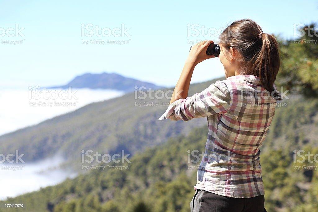 Hiker looking in binoculars stock photo