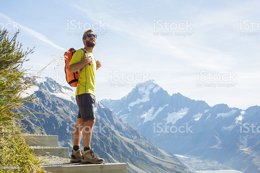 Hiker looks at mountain peak stock photo