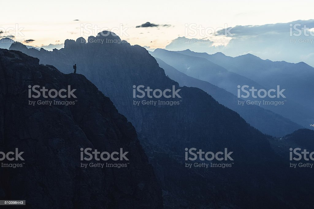 Hiker looks at mountains stock photo
