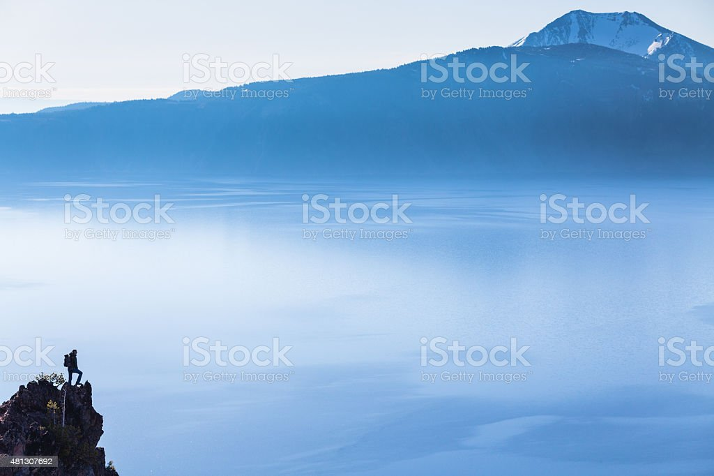 Hiker looks at the view of the Crater Lake, Oregon stock photo
