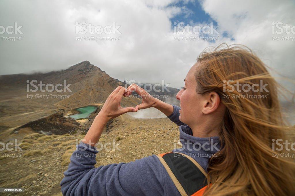 Hiker makes heart shape finger frame towards the Emerald lakes-NZ stock photo