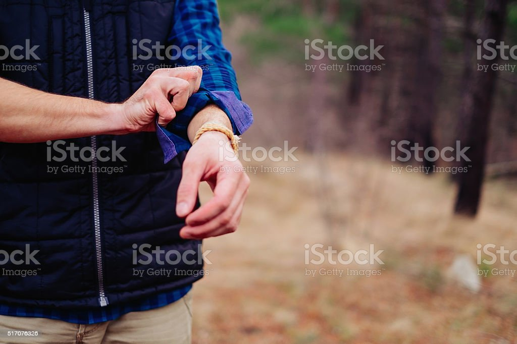 Hiker man rolling his sleeves stock photo