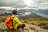 Hiker man sits on mountain top and looks at view