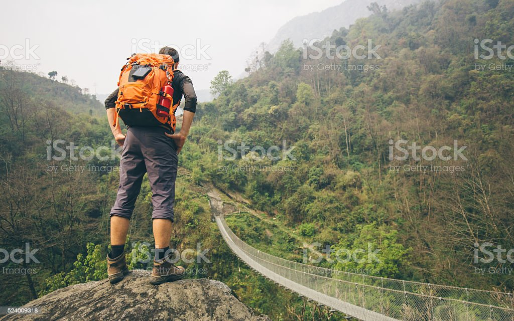Hiker man standing on rock stock photo