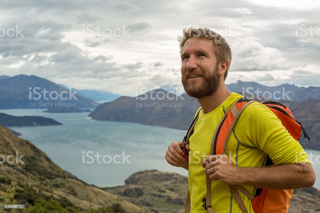 Hiker man stands on mountain top and looks at view stock photo