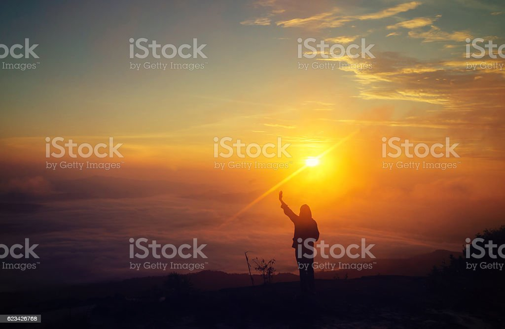 Hiker man stretching arms on the top of a mountain stock photo