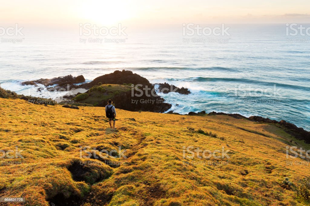 Hiker on a Headland watches the Sun Rise over the Ocean stock photo