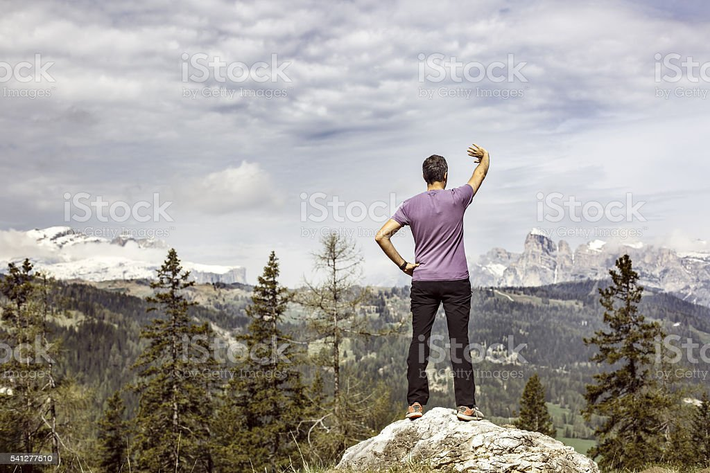 Hiker on a mountain top pasture looking for right way stock photo