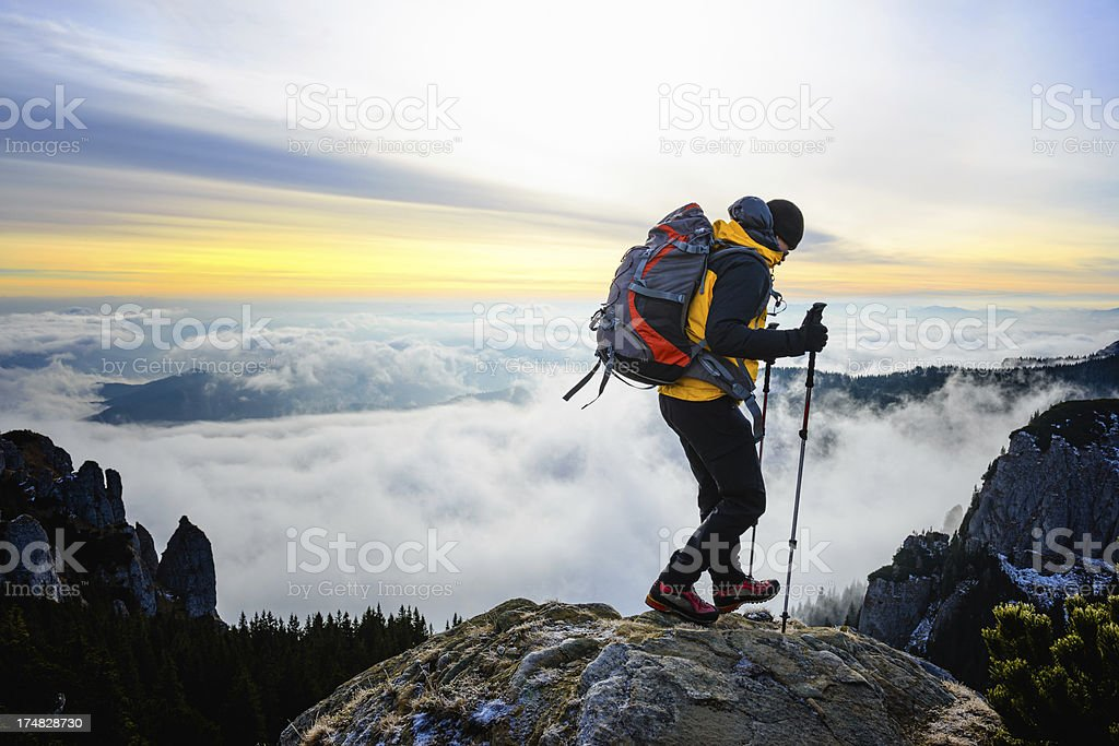 Hiker on a mountain with foamy sea in background royalty-free stock photo