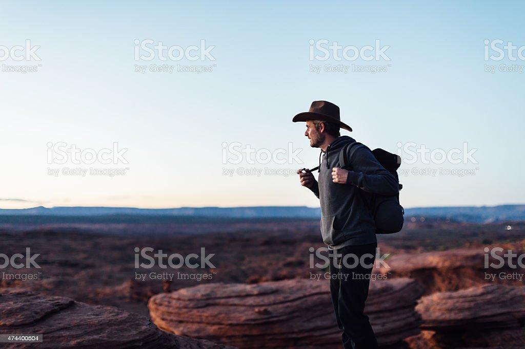 Hiker on edge of Grand Canyon cliff in Arizona stock photo