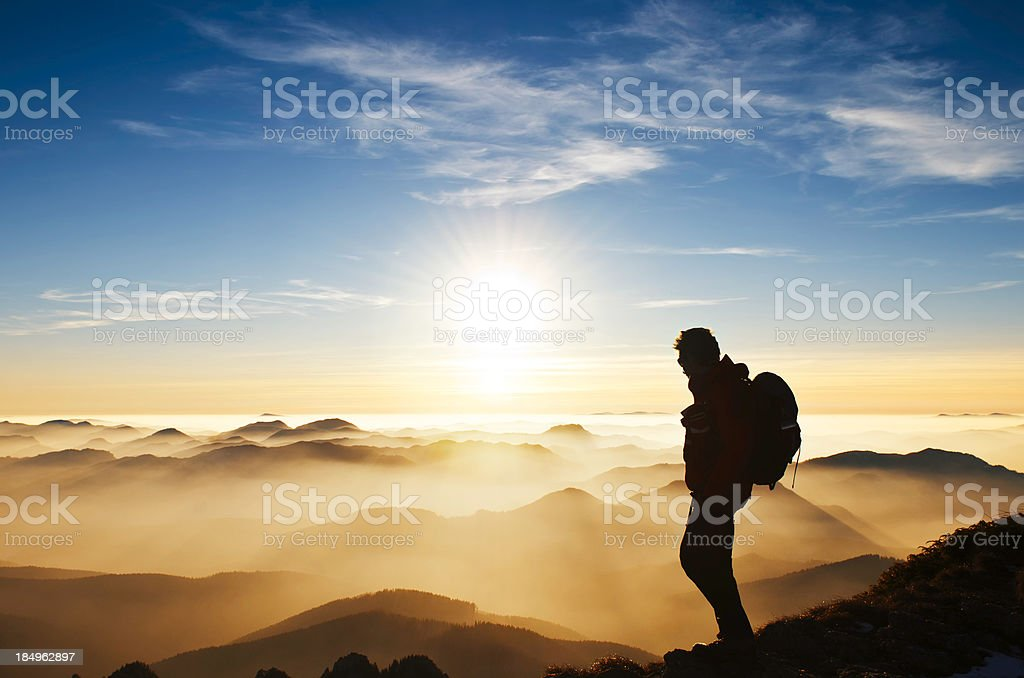 Hiker on mountain at sunset stock photo