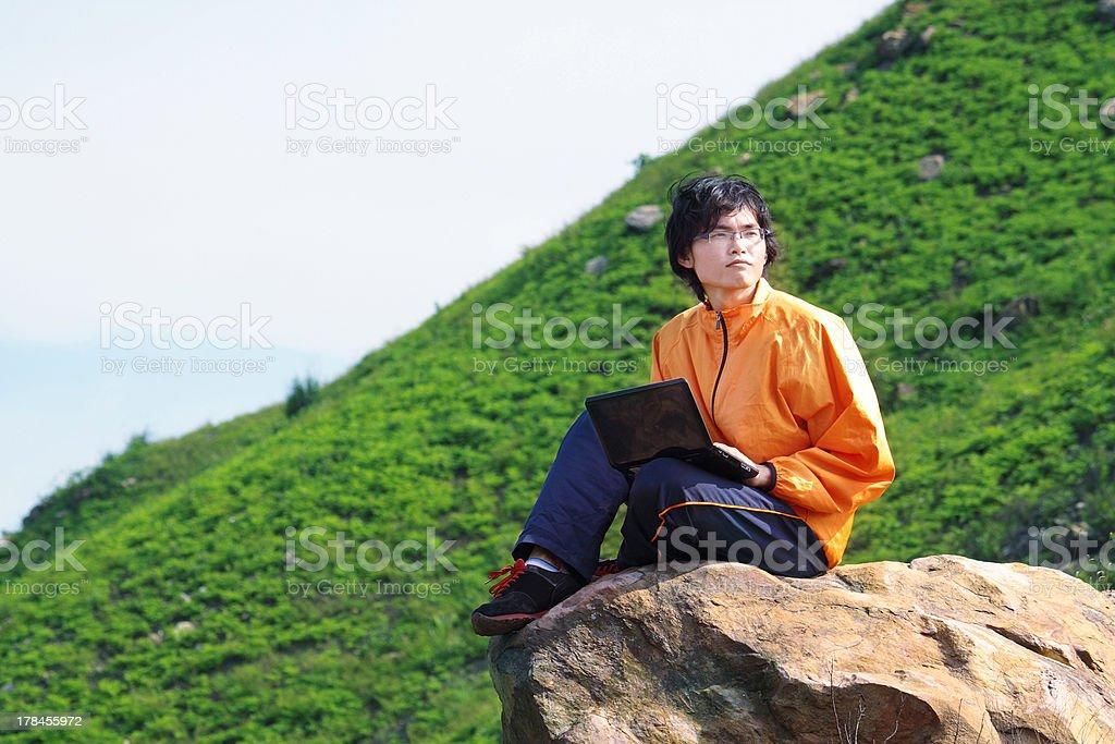hiker on mountain sitting near cliff's edge using laptop royalty-free stock photo