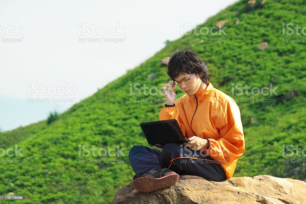 hiker on mountain sitting near cliff's edge using laptop royalty-free stock photo