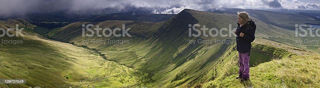 Hiker on mountain top admiring idyllic panoramic vista royalty-free stock photo