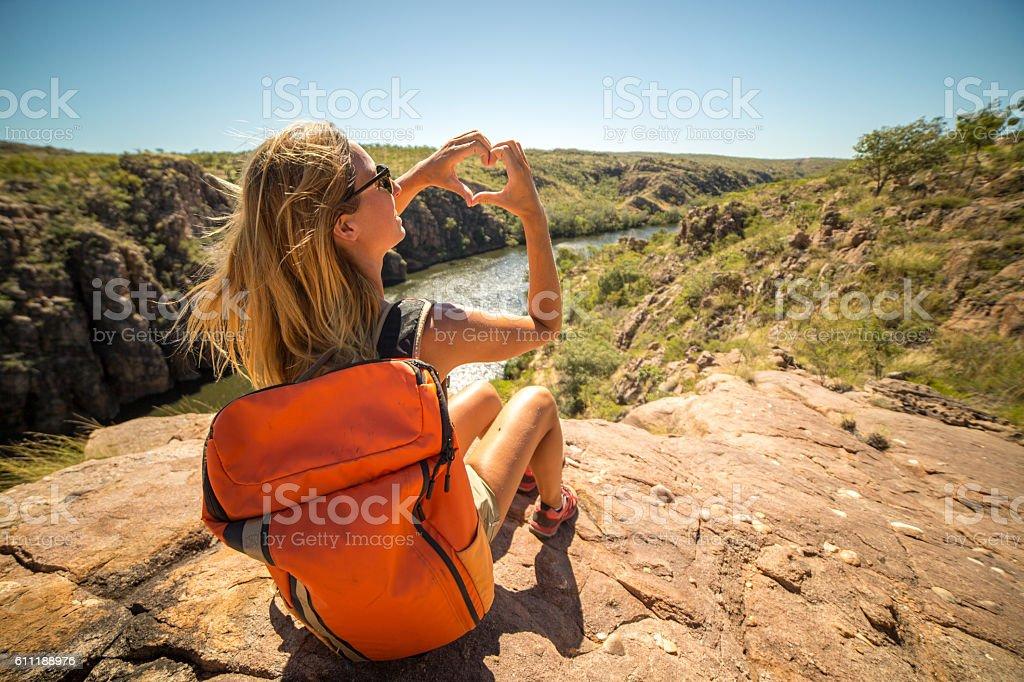 Hiker on mountain top makes heart shape finger frame stock photo