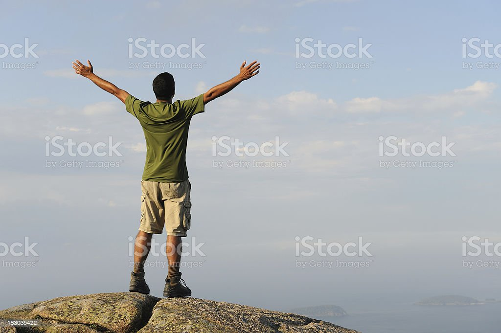Hiker on Mountain Top with Hands in Air royalty-free stock photo