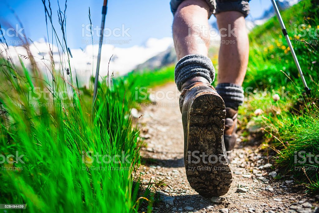 Hiker on mountain trail stock photo