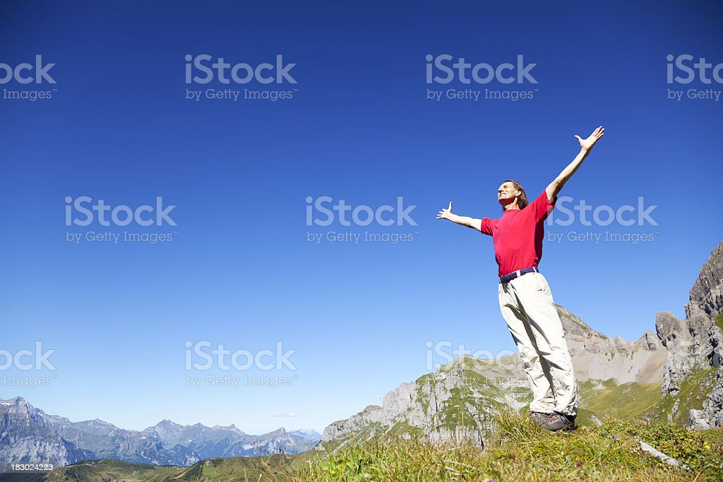 Hiker on Mountain with Outstreched Arms as Symbolising Positive Freedom stock photo