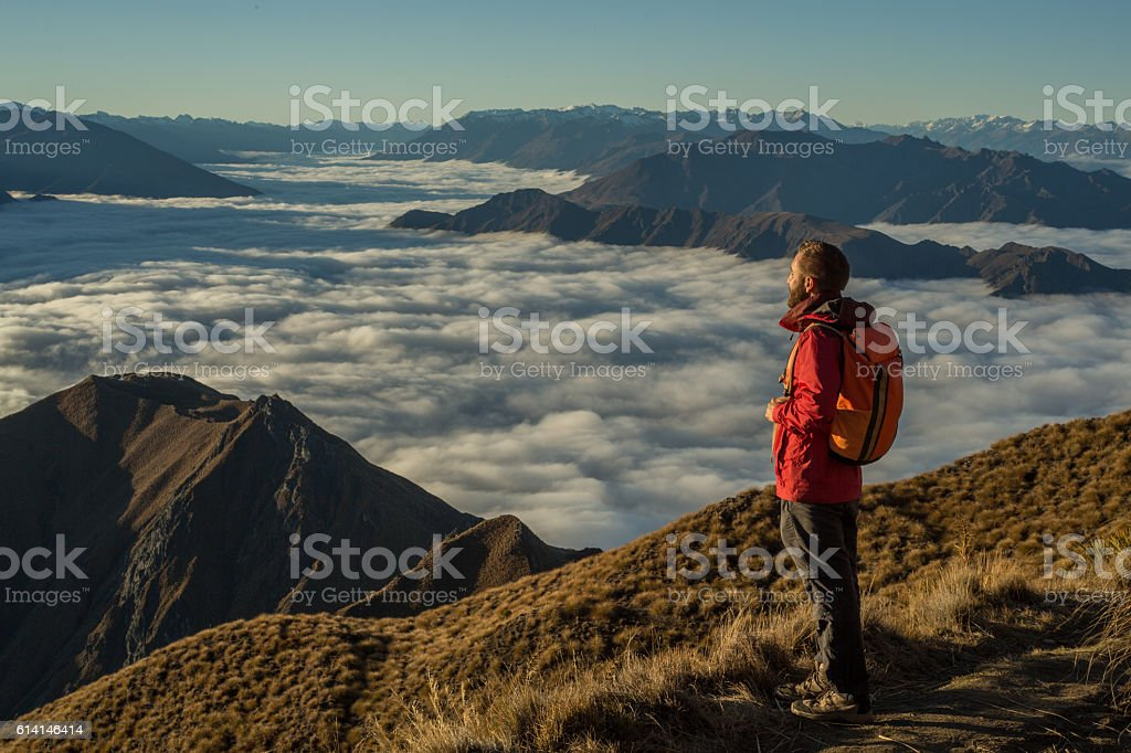 Hiker on moutain top contemplates view stock photo