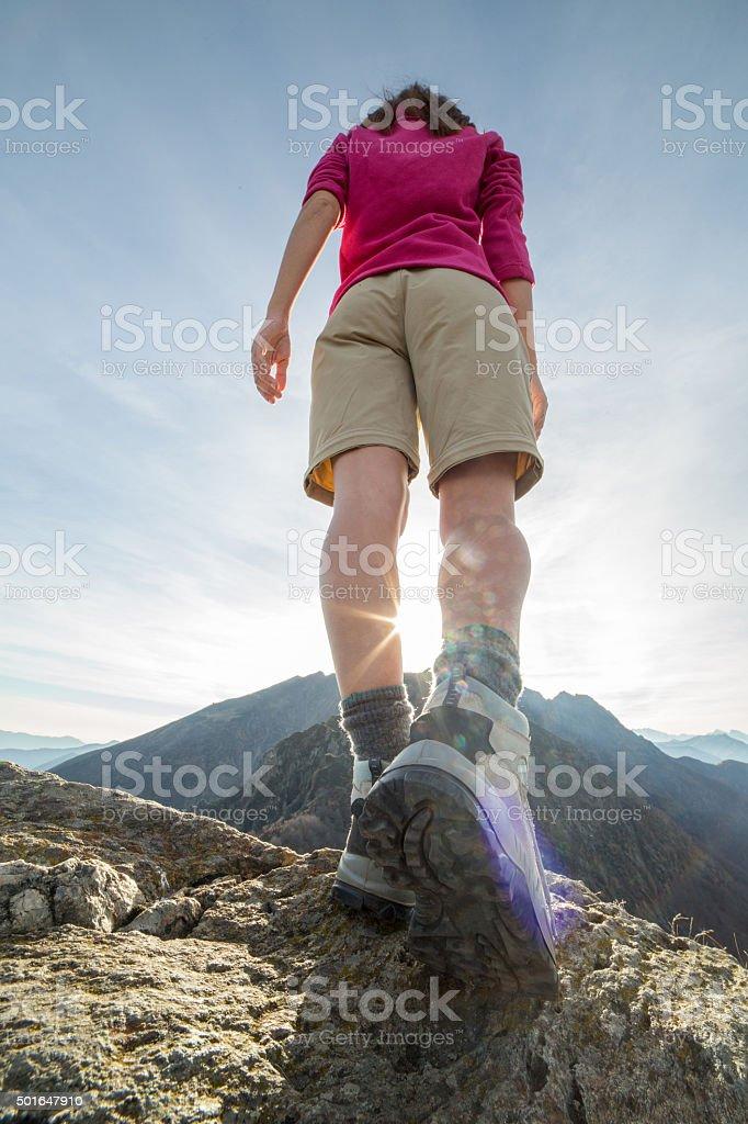 Hiker on ridge walking towards sunlight stock photo