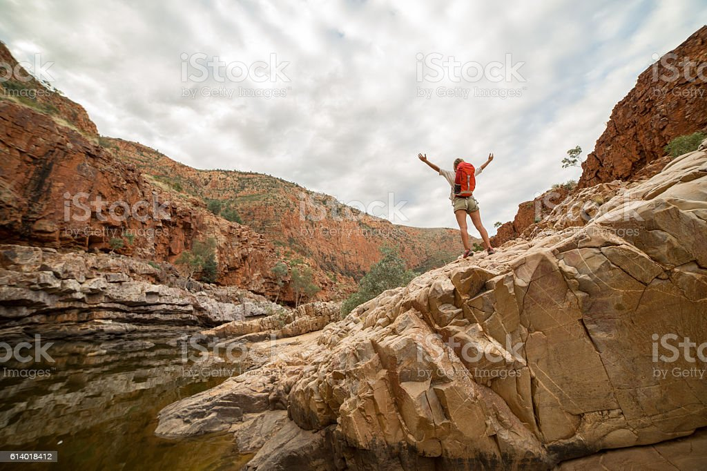 Hiker on rock arms outstretched stock photo