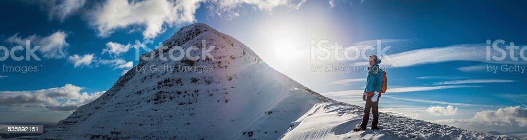 Hiker on snowy winter mountain peak panorama Brecon Beacons Wales stock photo