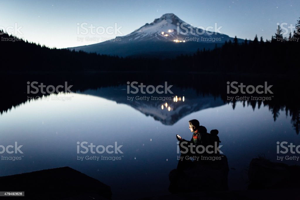 Hiker on the shore of the lake during twilight stock photo