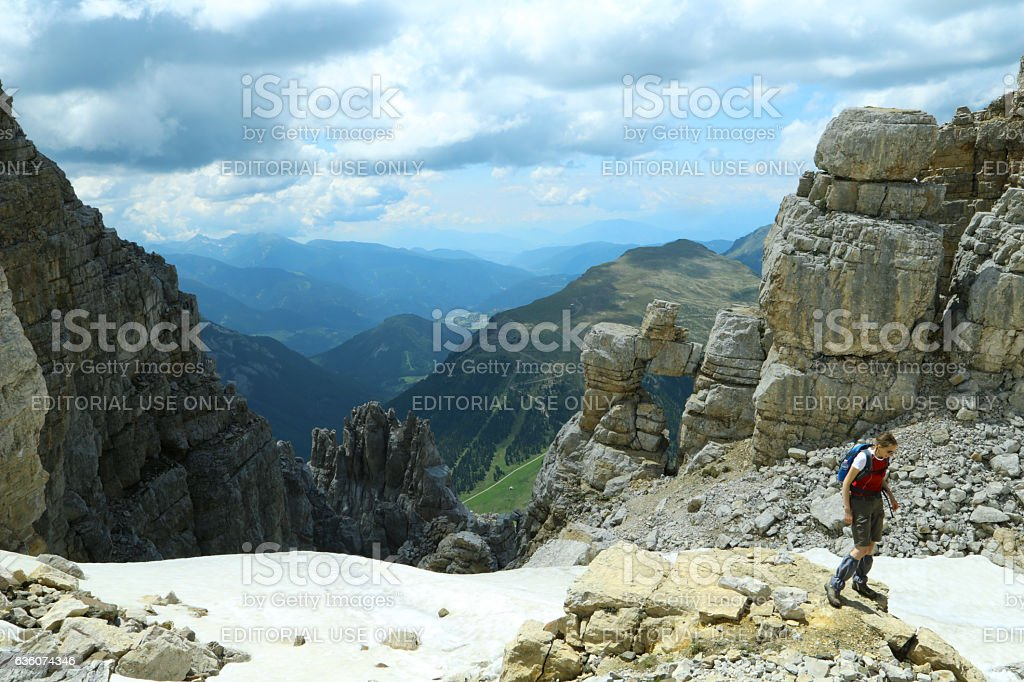 Hiker on the top of Latemar mountain, and natural window stock photo