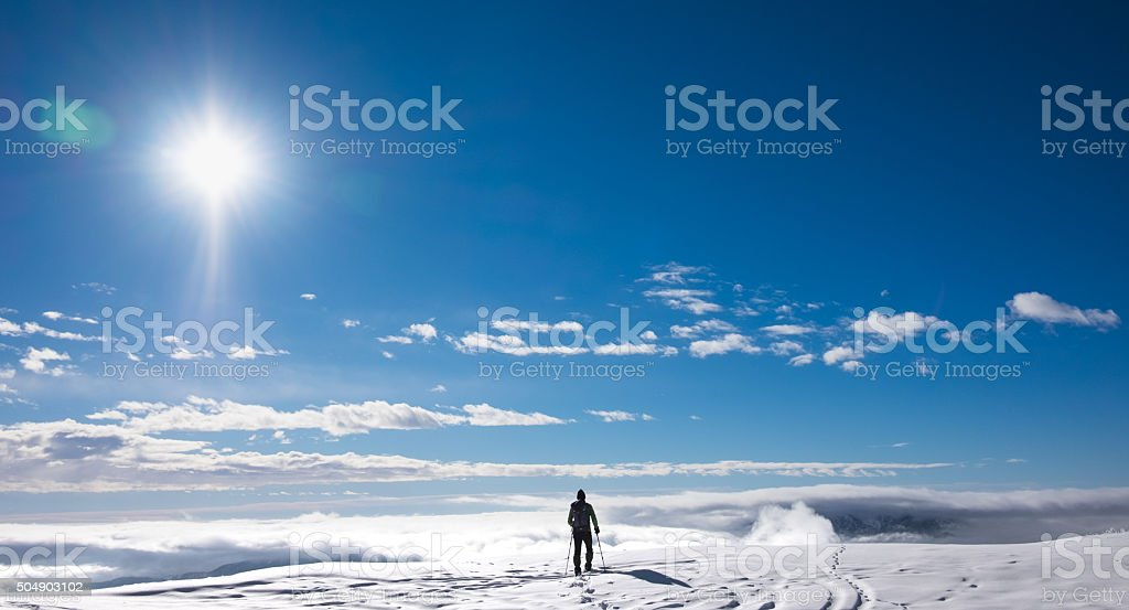 Hiker on top of snowy mountain stock photo